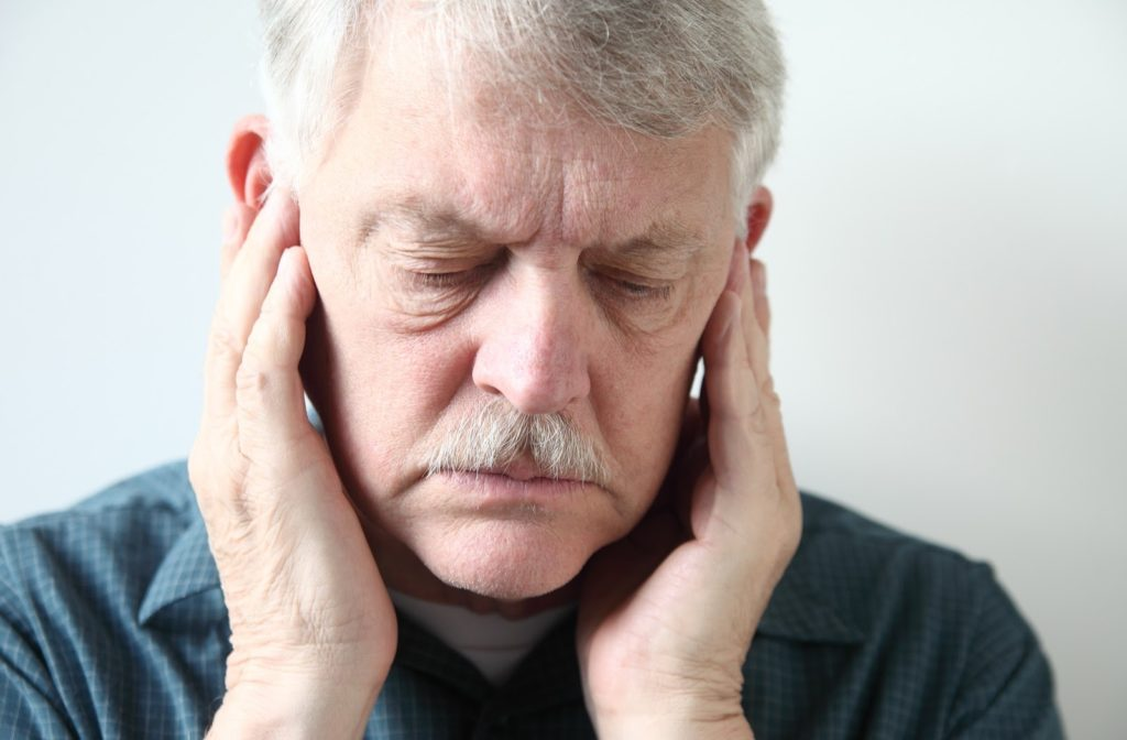 Older man showing mild signs of discomfort pressing both hands to the sides of his jaw at the TMJ
