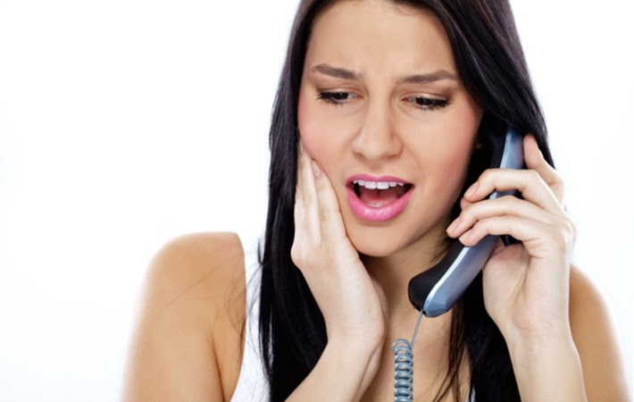 Woman on the phone with her dentist because she lost a dental crown