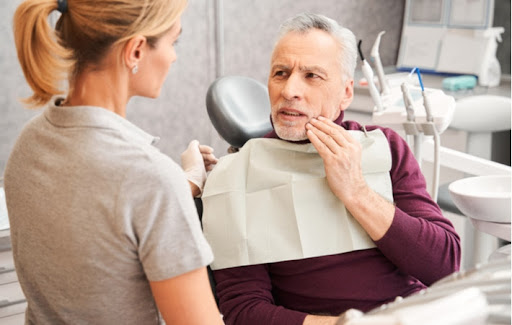 An elderly man talking with his dentist about his severe tooth pain in need of treatment