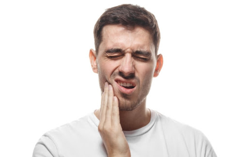 A man in front of a white background holding his face due to tooth pain